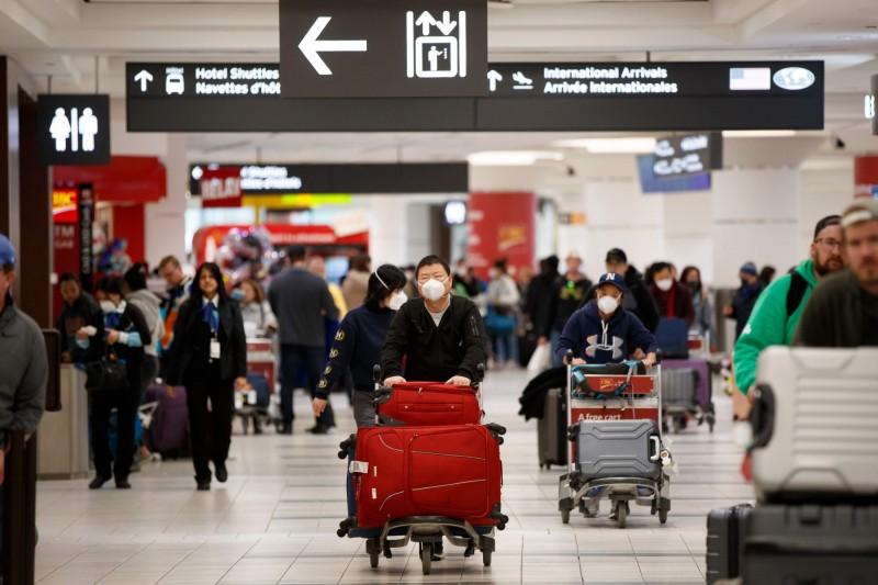 1名50多歲的男子從中國武漢飛往廣州,接著再搭機飛往加拿大多倫多時卻在機上發病,目前加國正全力追查與他有過接觸的乘客或服務人員。圖為多倫多機場入境區。(法新社)