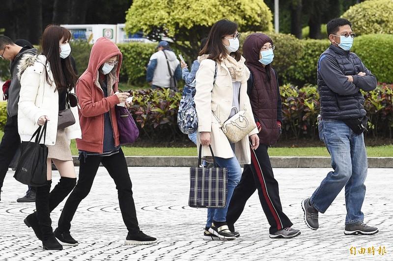 因應強烈冷氣團南下及防範武漢肺炎,民眾外出穿上保暖衣物及戴上口罩。(記者陳志曲攝)