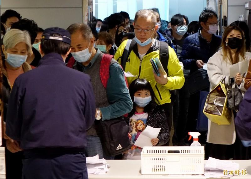 防疫人員在空橋門口收取旅客入境健康聲明卡。(記者朱沛雄攝)