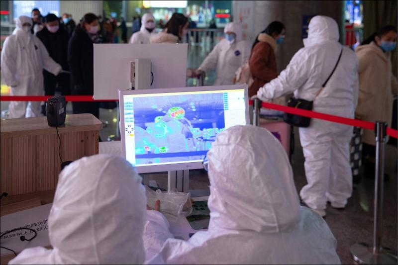 中國醫務人員1月27日在中國江蘇省南京市的南京火車南站使用紅外熱像儀檢查乘客的溫度。(歐新社)