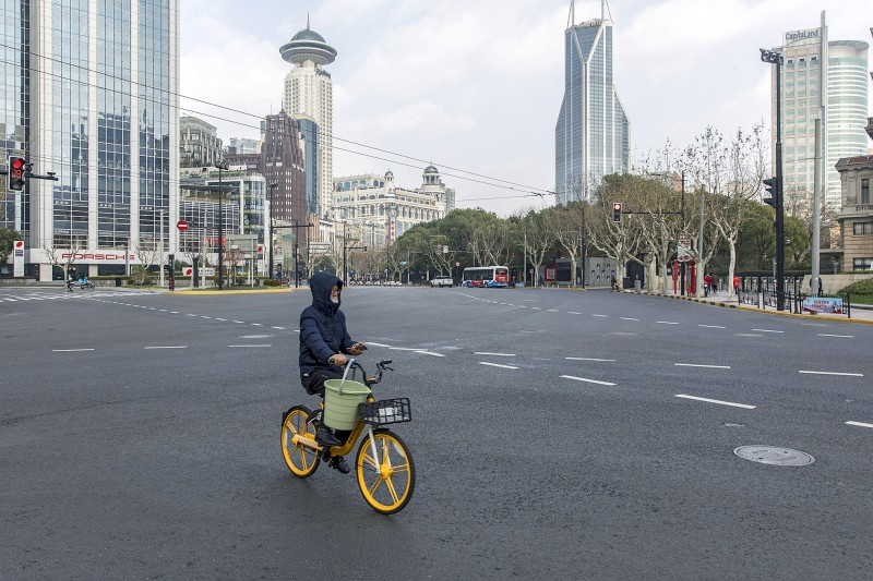 A man rides a bike though an almost empty Nanjing Road in Shanghai yesterday.  Photo: Bloomberg