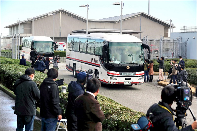 日本政府29日包機將206名日籍公民從武漢接回羽田機場,圖為下飛機的日僑搭車前往東京市區。(法新社)