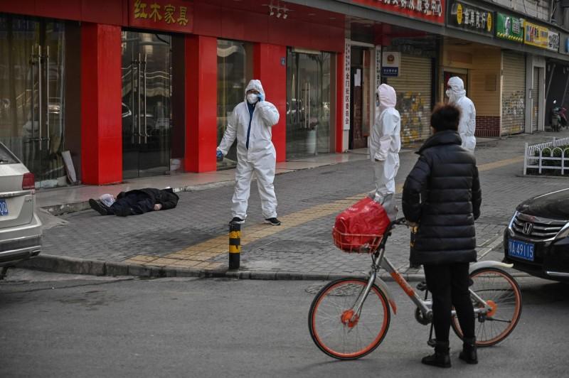 外媒目睹武漢民眾倒斃街頭,現場距離武漢第六醫院只有一個街區,當地民眾佇足圍觀。(法新社)