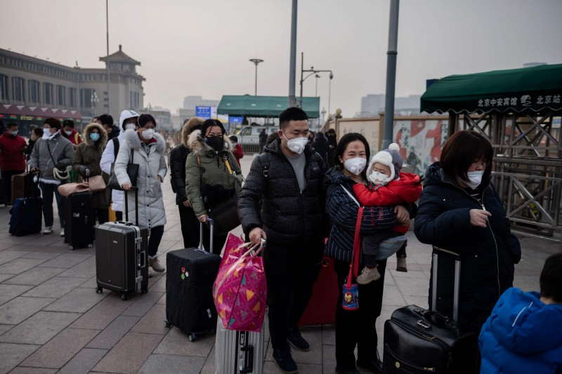 圖為中國北京民眾排隊搭車,戴著口罩防疫。(資料照,法新社)