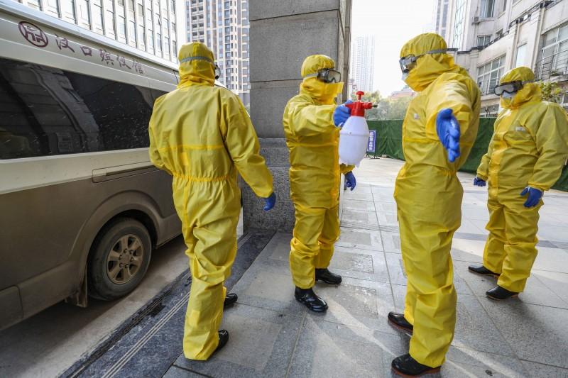 中國武漢金銀潭醫院收治的前99名確診病患當中有11人死亡,死亡率達到11%。圖為武漢運送遺體的人員正在互相消毒。(法新社)