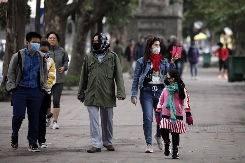 越南今日新增1起確診病例,是首起境內人傳人案例。圖為越南民眾戴口罩防疫。(歐新社)