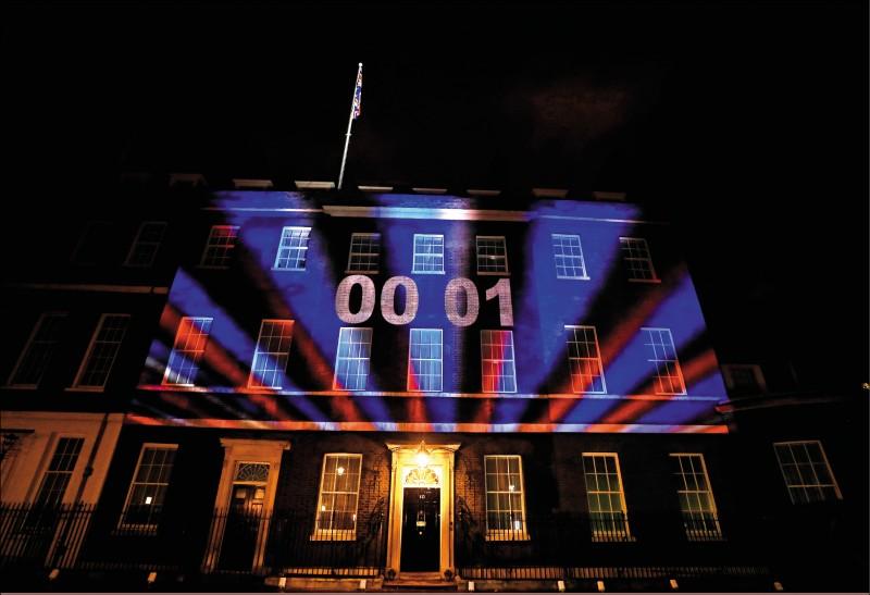 倫敦唐寧街十號的英國首相府外牆,於英國時間一月卅一日晚間,投影時鐘倒數計時該國正式脫歐的歷史性一刻。(美聯社)