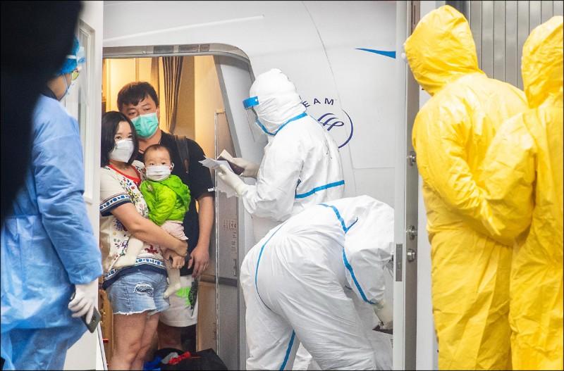 返抵中國的武漢居民下機前接受檢查。(歐新社)