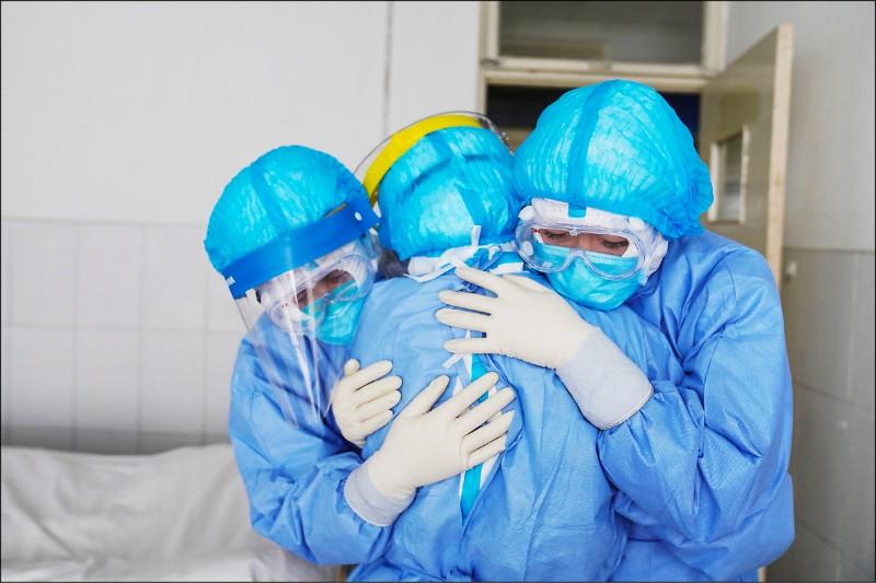 在醫療物資極度缺乏下,中國抗疫第一線的醫護人員之處境危險。圖為山東省鄒平市一間隔離病房內的三名醫護人員彼此相擁打氣。(法新社)