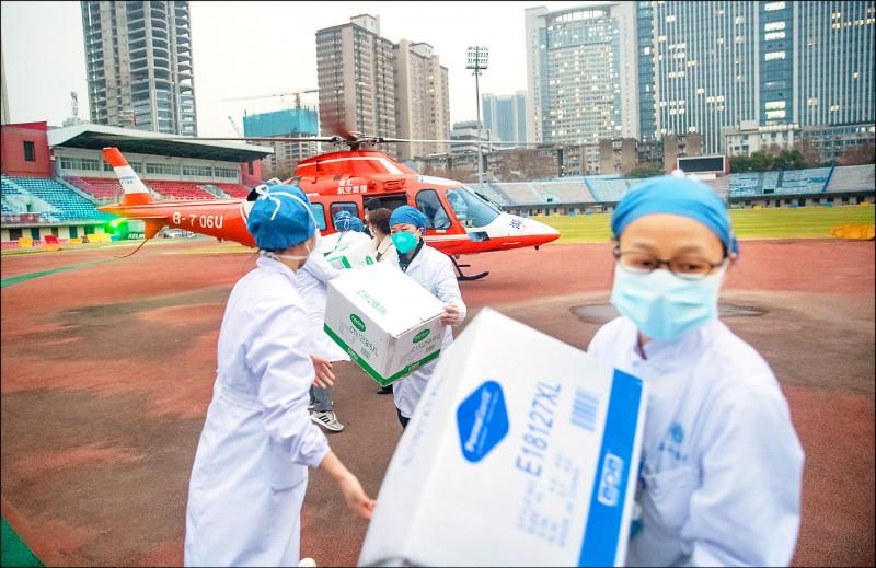 吉利德公司已向中國政府提供「瑞德西韋」,針對少數武漢肺炎患者進行測試,並與各國合作研究該藥可行性。圖為武漢華中科技大學同濟醫學院附屬協和醫院的醫護人員,從一架直升機上搬運物資。(歐新社)