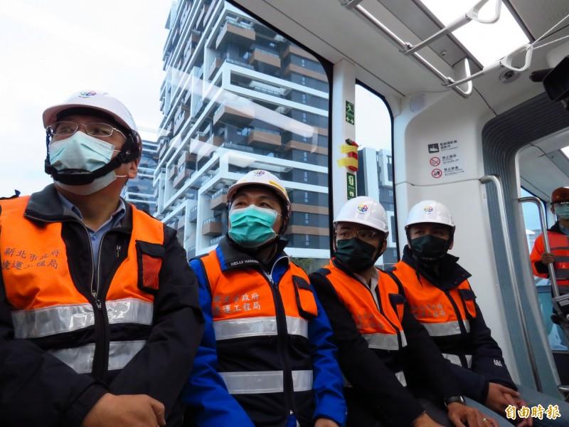 新北市長侯友宜(左二)今天下午視察淡海輕軌第一期藍海線工程,在車廂中戴著口罩。(記者陳心瑜攝)
