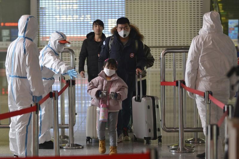 身穿防護裝的檢疫人員四日在南京車站監控旅客進出。(美聯社)