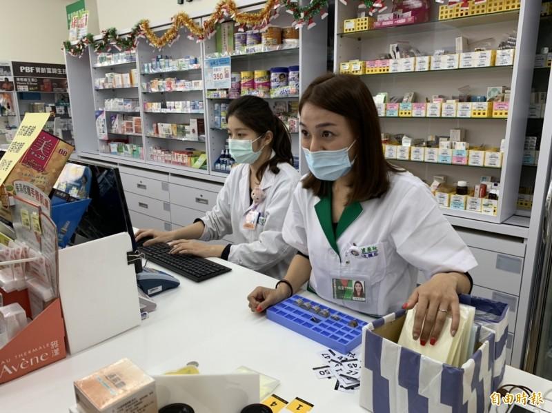位在花蓮市中山路的佑全藥局準時2點發放號碼牌販售口罩,記者實測排隊拿到49號,不到20分鐘就至櫃台買到口罩。(記者王峻祺攝)