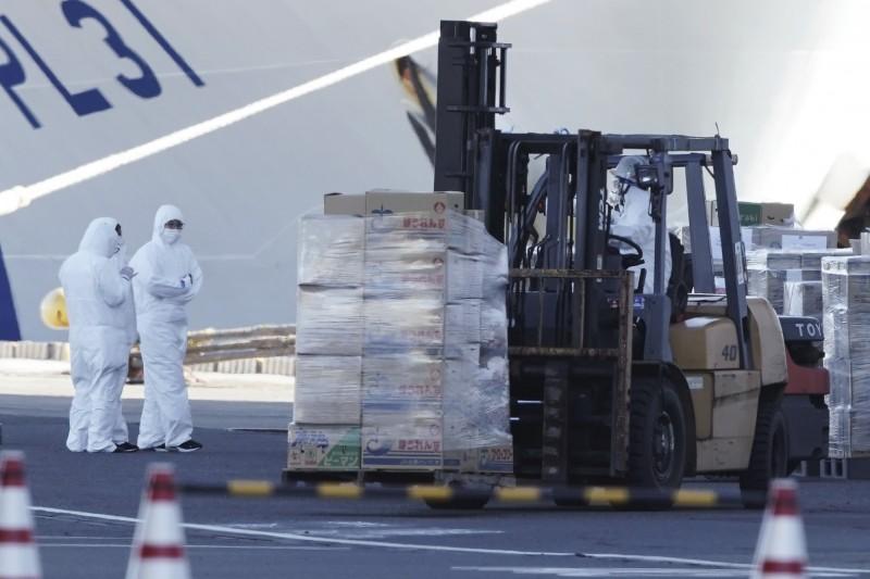 日方人員防護衣全副武裝運送物資給「鑽石公主號」。(美聯社)