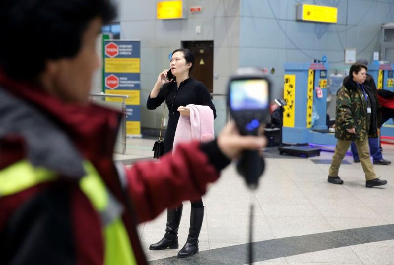 中國的鄰國哈薩克今(6)日宣布,禁止向中國出口口罩,同時暫停與中國的郵務來往。圖哈薩克防疫人員在機場使用熱像儀掃描來自中國的旅客。(路透)