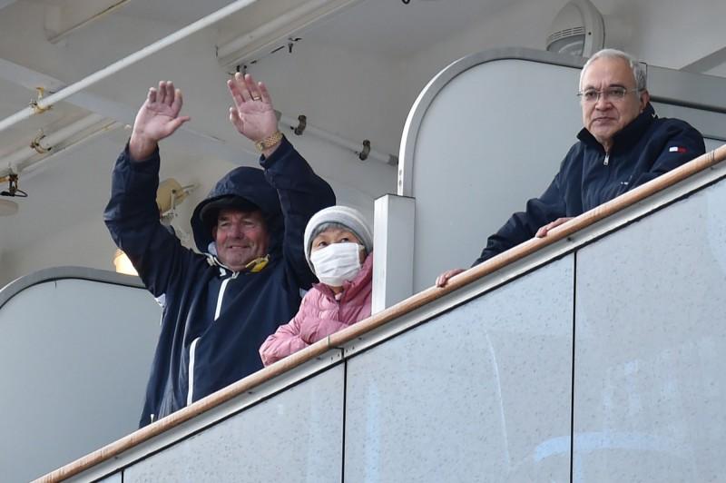 船上乘客到房間陽台透氣,向陸地張望,向聚集在碼頭上的人群揮手。(法新社)
