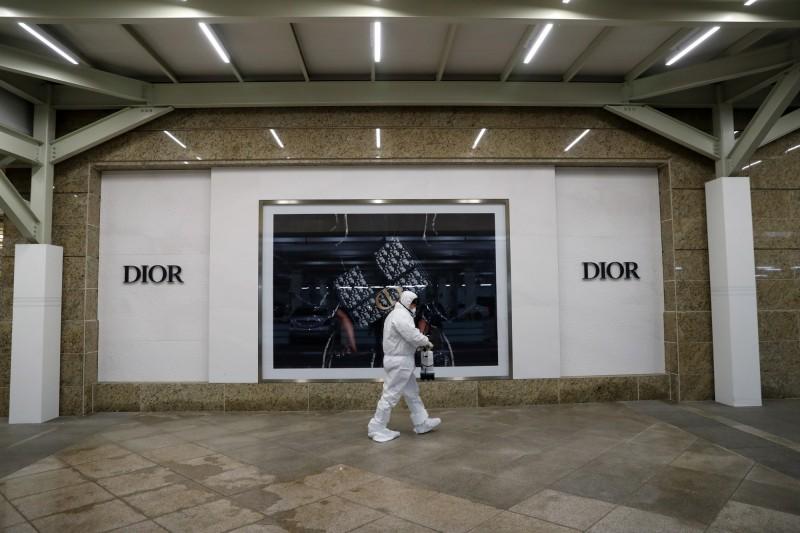 南韓樂天百貨總店因1名中客確診,今宣布暫時營業,圖為消毒人員進入總店。(歐新社)