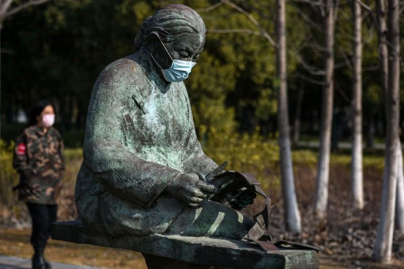中國武漢肺炎疫情嚴重,各地的雕像都紛紛被戴上口罩,似乎在提醒民眾出門千萬別忘了口罩。圖為江蘇淮安母愛公園。(法新社)