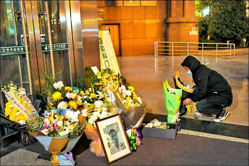 一名民眾七日在中國湖北武漢市中心醫院外擺放花束,悼念武漢肺炎吹哨者之一李文亮醫師在該院病逝。(歐新社)