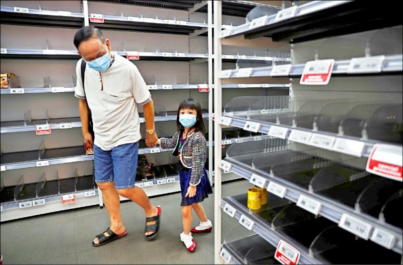 新加坡一對父女八日戴著口罩進入當地超級市場,打算購物補貨,卻見貨架上空空如也。(路透)