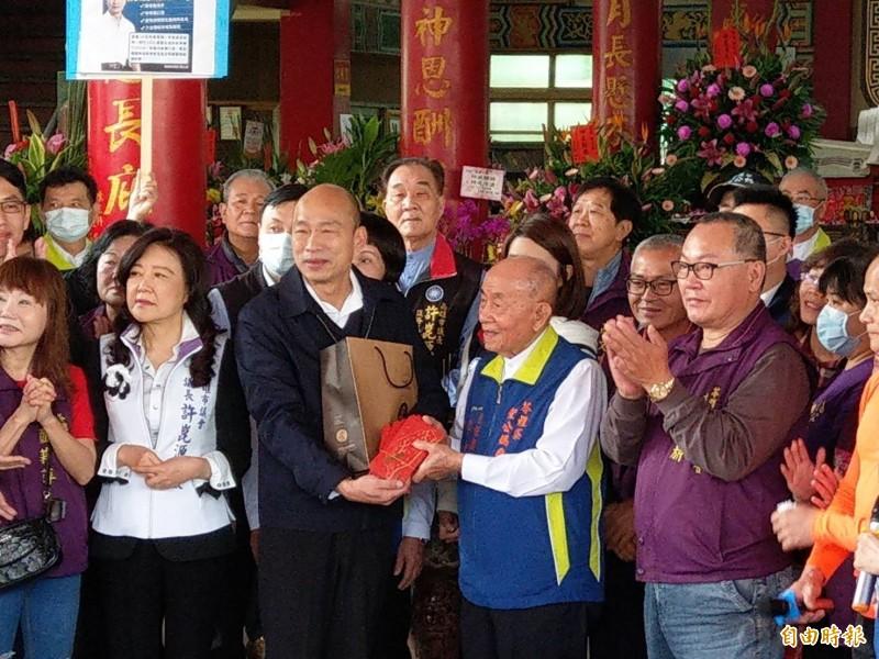原堅持戴口罩的高雄市長韓國瑜(左3),今到苓雅區萬應公廟參拜,下車就脫下口罩,致詞後並送福袋給廟方人員。(記者方志賢攝)
