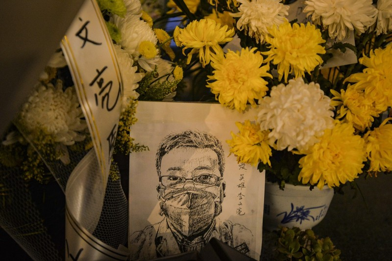 中國民眾突破禁令,在李文亮醫師生前服務的醫院及住家前擺放鮮花悼念。(歐新社)