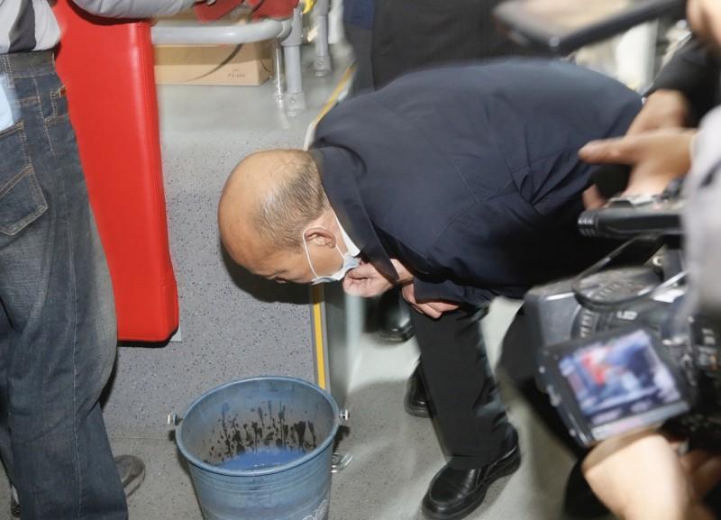 韓國瑜7日下午視察公車消毒作業,在媒體面前拉下口罩,湊近裝有消毒水的桶子。(中央社)