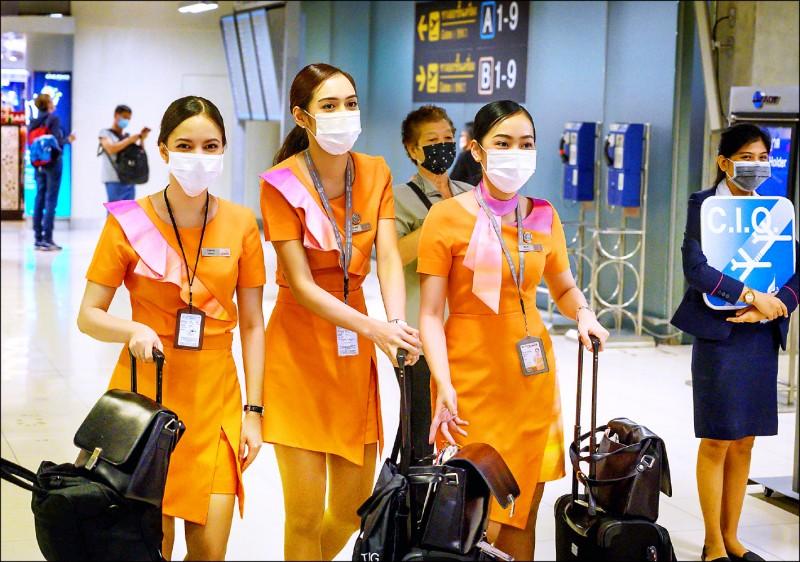 戴著口罩的泰國微笑航空空服員,九日在曼谷蘇凡納布國際機場,經過一名手持寫有中國入出境檢驗檢疫局字母縮寫告示牌的工作人員。(法新社)