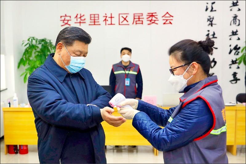中國新華社十日報導,中國國家主席習近平在北京訪視基層防疫工作。圖為他在北京朝陽區安華里社區居委會聽取簡報前,戴口罩測量體溫。(新華社)