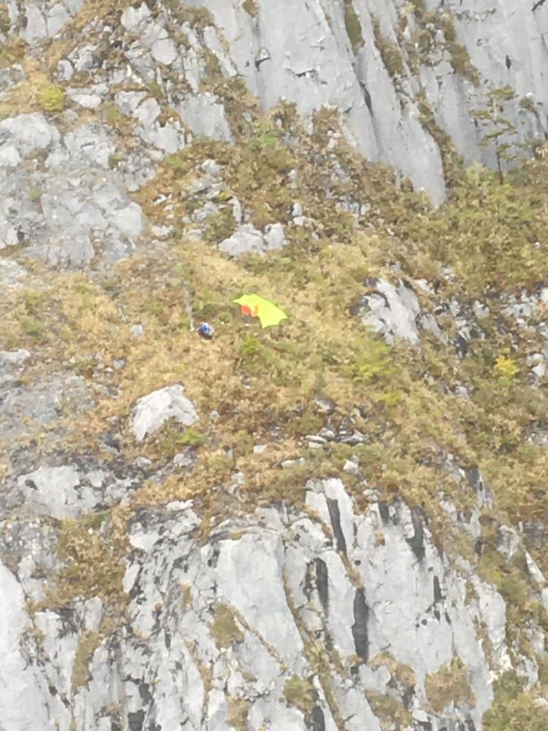 張姓及楊姓山友挑戰針山峭壁,因連日大霧卡在海拔約1800公尺的營地,上不去也下不來,幸好今天空勤直升機順利完成不可能的「絕壁任務」。(消防局提供)