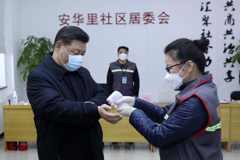 中國國家主席習近平,昨現身北京視察、慰問,不過照片曝光後,其中一張習戴口罩,由醫護人員對手腕測量體溫的畫面,引起網友非議。(美聯社)
