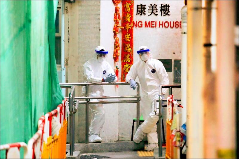 身穿全套防護裝備的檢疫人員對新界青衣的康美樓大樓進行檢查和消毒。(美聯社)