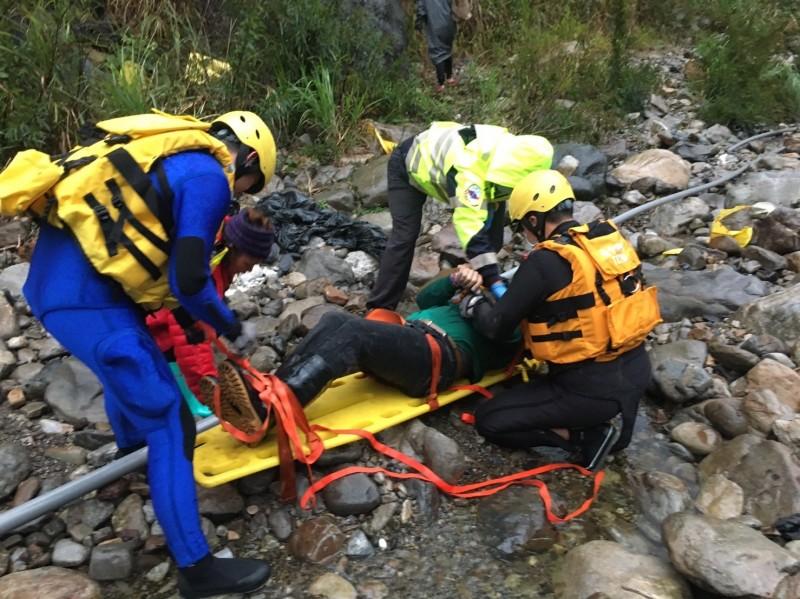 消防人員用擔架及繩索將鄭保雄的遺體抬到車輛可以抵達的路邊。(記者歐素美翻攝)