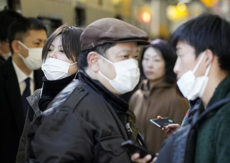和歌山縣今(13)日出現首個武漢肺炎病例,是當地一名50多歲醫生。圖為日本街頭行人戴著口罩。(歐新社)
