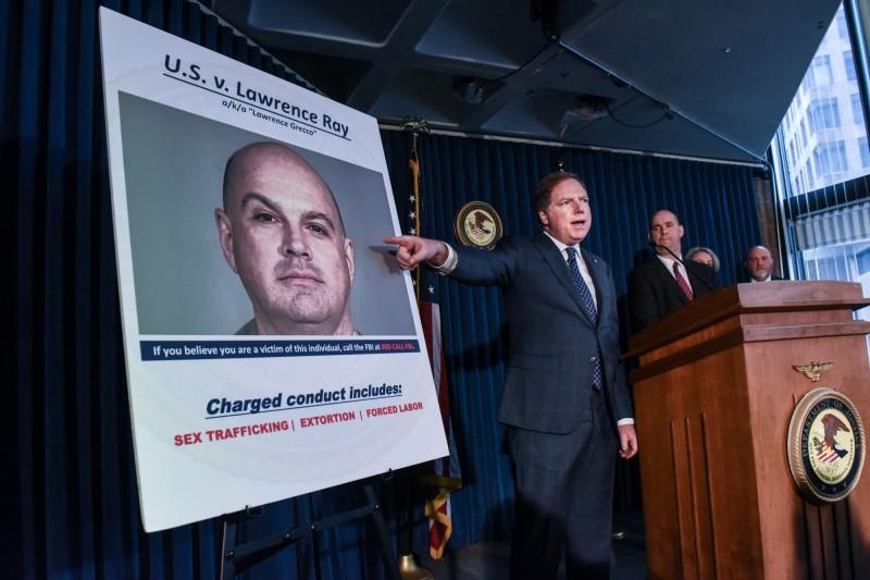 美國紐約州名校學生家長雷伊(Lawrence Ray,圖中海報上男子)被指控對5名學生勒索近3000萬元,並至少逼迫1名女生賣淫長達4年。(法新社)