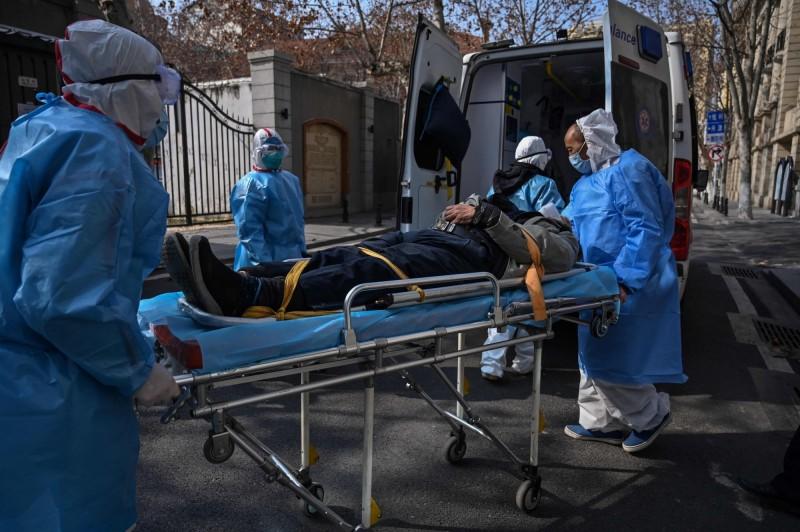 圖為武漢市醫護人員協助將患者送往醫院情況。(法新社)