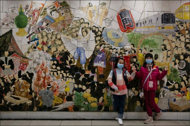 兩名來自中國的小觀光客,今年1月30日戴著口罩,在東京淺草車站的壁畫前擺姿勢拍照。(美聯社檔案照)