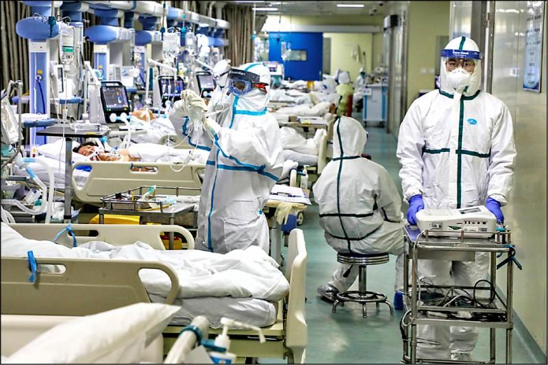 武漢市的疫情嚴重,身穿防護衣的醫護人員正照料被隔離治療的確診病患。(美聯社)