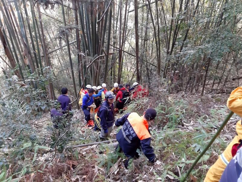 搜救人員合力在陡坡將佐藤先生遺體搬上來。(南投縣消防局提供)