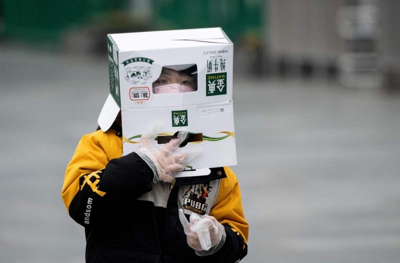 上海火車站一名孩童頭戴紙箱。(法新社)