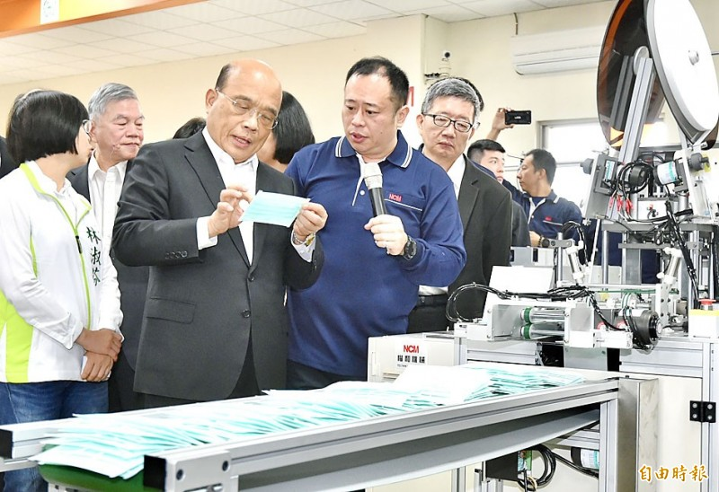 Premier Su Tseng-chang, third left, examines a mask at Nonwoven Converting Machinery Co's factory in New Taipei City's Yingge District yesterday accompanied by Minister of Economic Affairs Shen Jong-chin, second left, and Democratic Progressive Party Legislator Lin Shu-fen, left.  Photo: Tu Chien-jung, Taipei Times