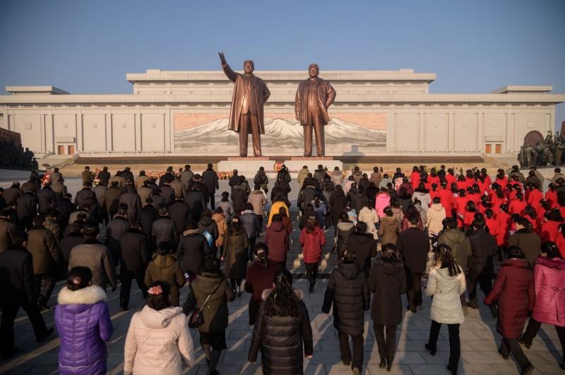 南韓媒體報導,北韓一名貿易官員到過中國之後,回國沒有遵守隔離命令,立即遭到槍決。圖中,北韓人民聚集在金正恩及金日成雕像前。(法新社檔案照)