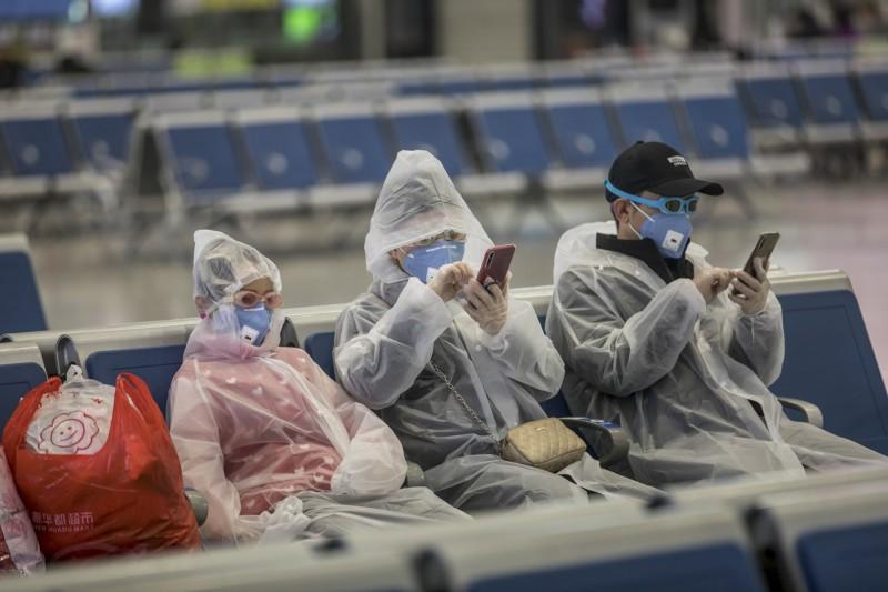 中國上海的虹橋高鐵站,民眾戴著口罩和臨時保護裝備等車。(歐新社)