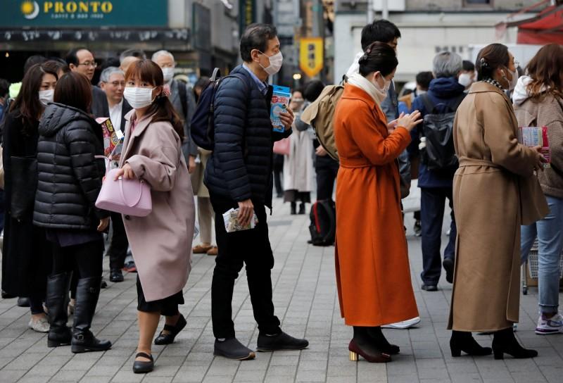 台灣今將日本旅遊疫情建議則升為第一級「注意(Watch)」。圖為14日東京藥局前戴口罩民眾排隊買口罩。(路透)
