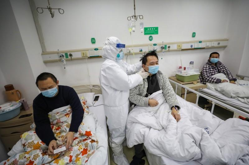 中國武漢肺炎確診病例昨(13日)大幅增加1萬4840人、死亡242人,WHO對此仍表示,武漢肺炎死亡率或嚴重程度沒有重大變化。圖為中國武漢金銀潭醫院的醫護人員,在為新型冠狀病毒重症患者做檢查。(歐新社)