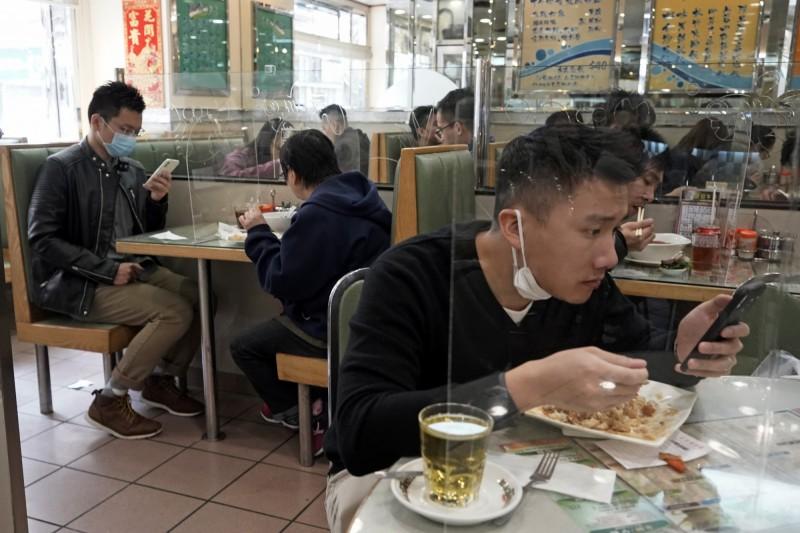 香港餐廳業者自製塑膠板,豎在桌上以隔開同桌的客人。(美聯社)