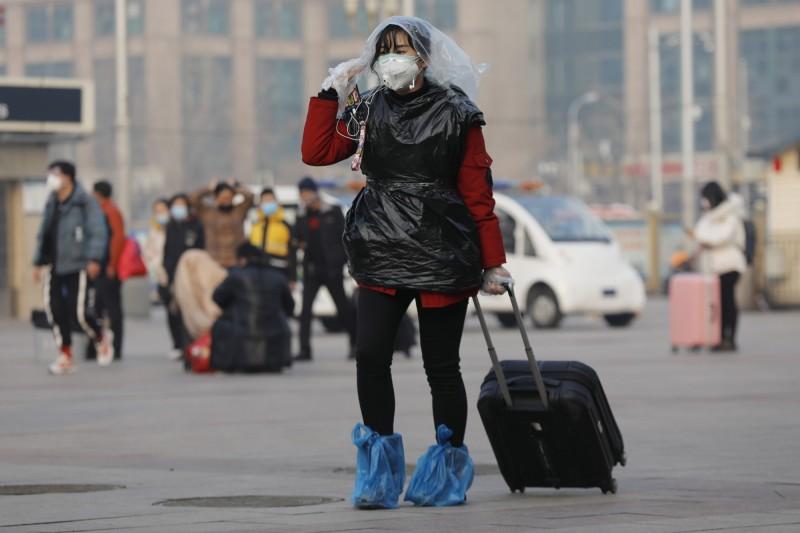 中國北京一名女子用塑膠袋包覆身體。(歐新社)