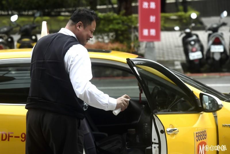 政府配發口罩,個人計程車駕駛人可向相關計程車公會或職業工會購買。圖為計程車司機消毒車身防疫。(資料照)