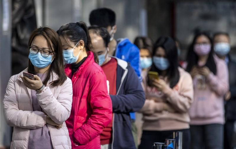 圖為中國廣州中籤的民眾在藥局外排隊買口罩。(歐新社)