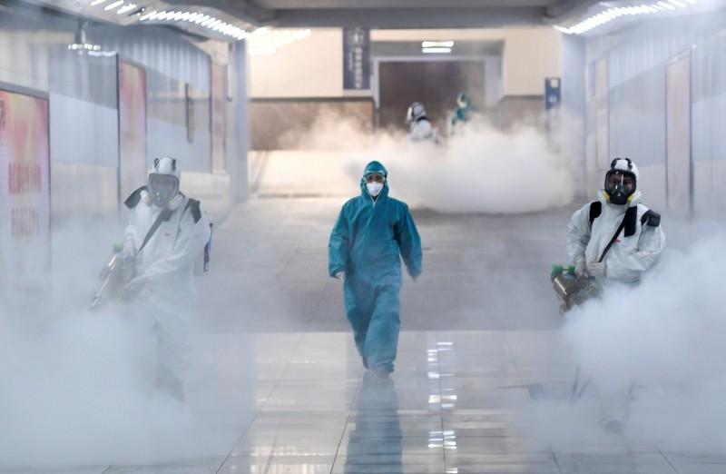 中國湖南省傳出有官員害怕被感染,攜家人到泰國避難,現已被撤職處分。圖為湖南省工作人員為火車站消毒。(路透社)